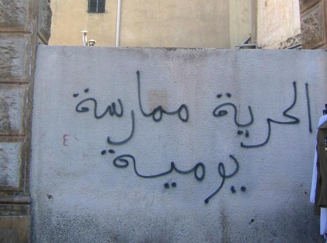 """غرافيتي """"الحرية ممارسة يومية"""" في شارع الحبيب بورقيبة، تونس. تاريخ التقاط الصورة 24 حزيران 2011"""